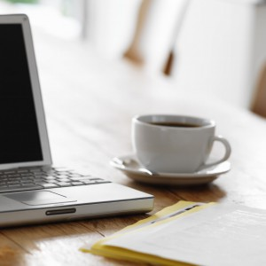 Laptop on Kitchen Table with Cup of Coffee